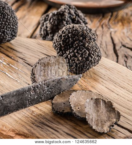 Cutting of black truffle on the wooden board.
