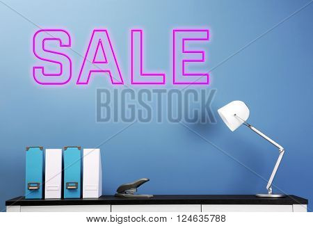 Sale concept. Wooden chest of drawers with folders, lamp and stapler on blue wall background