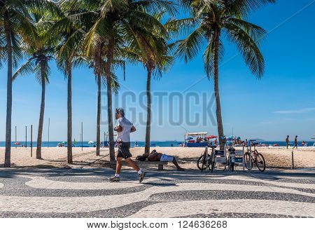 Rio de Janeiro Brazil - December 21 2012: People run around and relax on Copacabana sidewalk at Rio de Janeiro. New Age writers cite Mayan and Aztec calendars which predicted the end of the age on Dec 21 2012.