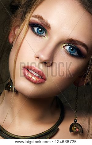 Close-up beauty portrait of funny girl with big blue eyes. Modern multicolored smokey eyes make-up. Studio shot.