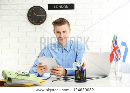Young man using tablet in the office of travel company