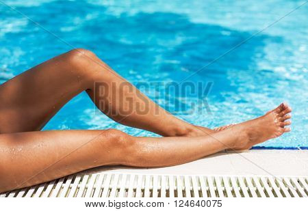 Wet tanned woman legs on the edge of swimming pool.