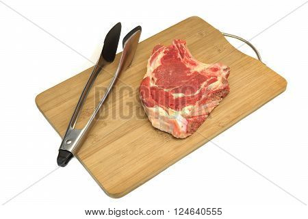 Raw Beef Steak,  Tongs On The Wood Cutting Board Isolated