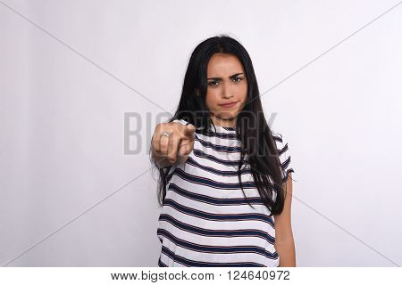 Young beautiful woman pointing to camera. Isolated white background.