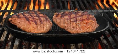 Two Browned Strip Beef Steaks In The Cast Iron Frying Pan On The Hot BBQ Charcoal Grill With Bright Flames In The Background Top View Close-Up