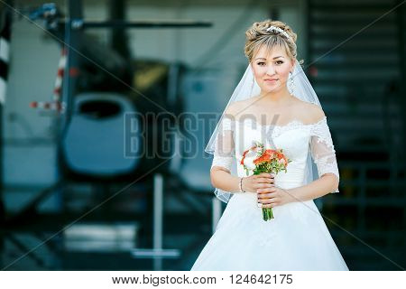 The bride with a wedding bouquet on a background of a helicopter in the hangar