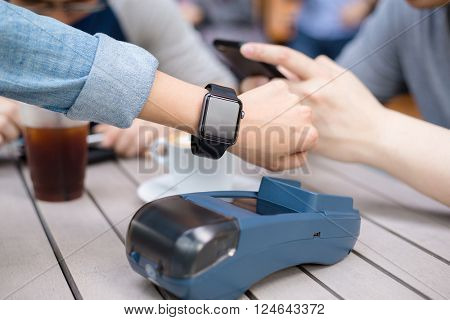 Woman pay by smart watch on pos machine