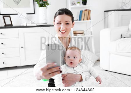 Businesswoman make selfie on mobile phone with baby boy in room