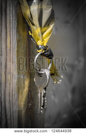 Metal keys hanging from a wooden pole.