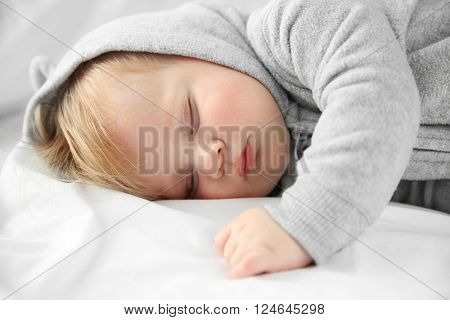 Little baby boy in grey pajamas sleeping on the bed, close up