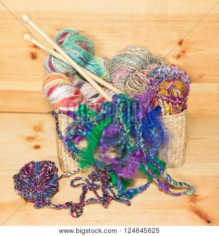 Basket with fancy art yarns and knitting needles on wood.