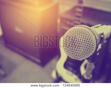 Black and white photo and lighting of The microphone in a recording studio or concert hall with amplifier in out of focus background. : Vintage style and filtered process.