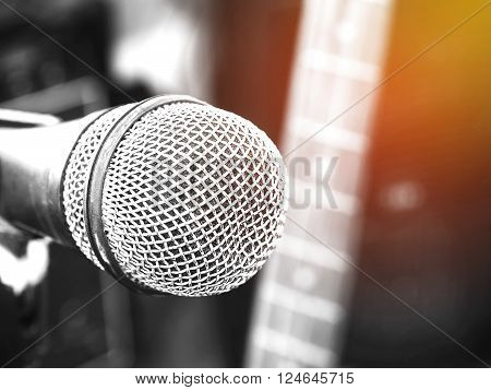 Black and white photo and lighting of the microphone in a recording studio or concert hall with electric guitar in out of focus background. Vintage style and filtered process.