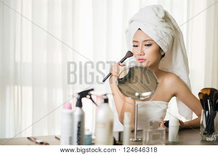 Beautiful Vietnamese  girl doing make-up in the morning