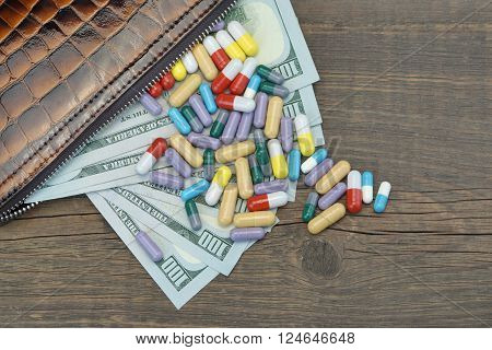 Wallet With Us Dollar Cash And Medication On Wood Background