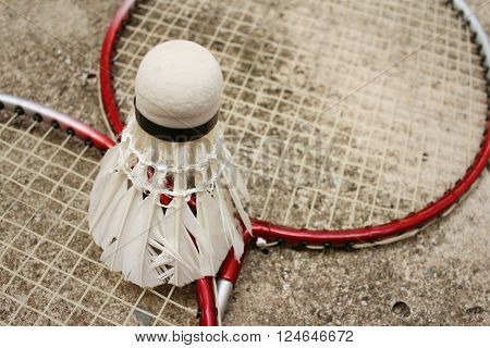 Shuttlecock and badminton racket on cement background. ** Note: Shallow depth of field