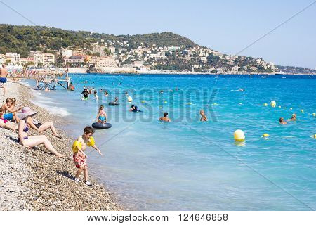 NICE FRANCE - AUGUST 23, 2015: Tourists enjoy the good weather at the beach on August 23 2015 in Nice France. The beach and the waterfront avenue Promenade des Anglais are full almost all the year.
