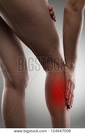 Woman massaging her painful leg calf. Joint injury or disease