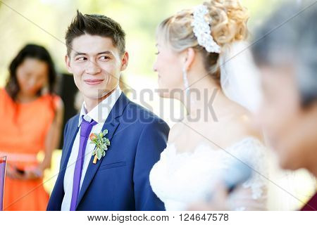 Happy groom is looking at the bride during a wedding ceremony among the guests of the crowd, ceremonial part, vows.