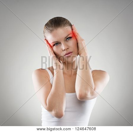 Young woman having vertigo problem or brain disease. Pretty Caucasian female touching her painful temples.