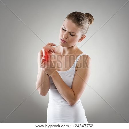 Woman touching her injured wrist in pain. Hand sprain concept