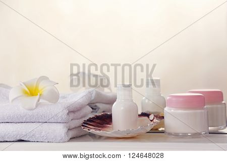 White towels with cream and tropical flower on a shelf in bathroom