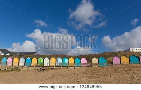 Traditional colourful English seaside scene with beach huts on the beach and blue sky with pastel colours