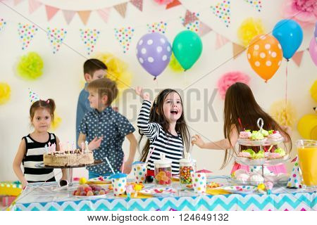 Happy group of children dancing at birthday party