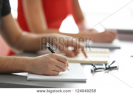 Student's hand writing in exercise book at the table