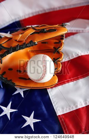 Baseball and glove on background of American flag. Popular sport concept