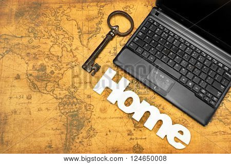 Home Sign, Key And Laptop On Old Map Background