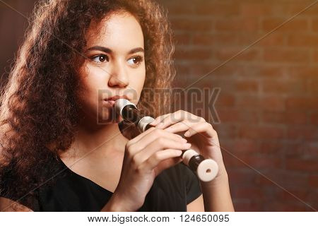 Beautiful young woman playing on recorder over brick wall background