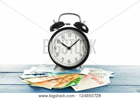 Alarm clock and money on wooden table.