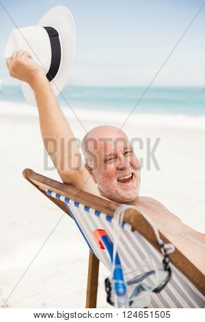 Senior man holding his sunhat on a sunny day