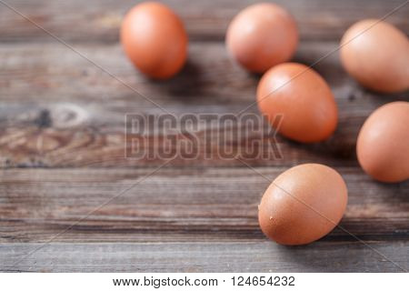 Brown eggs on a rustic wooden table. Focused on nearest egg.