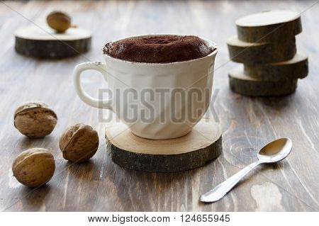 Quick chocolate coffee cake in a cup and walnuts on a rustic wooden background.