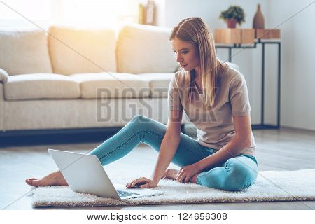 Staying connected at home. Beautiful young woman using her laptop while sitting on carpet at home