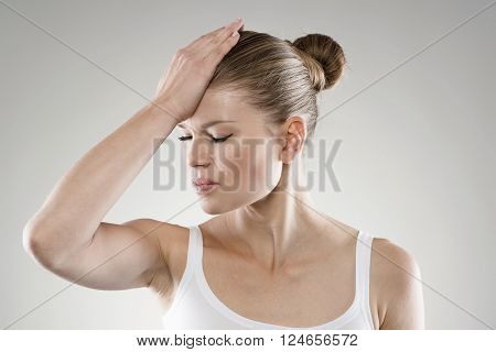 Close-up portrait of young stressed woman touching her forehead in pain. Memory loss and headache concept.