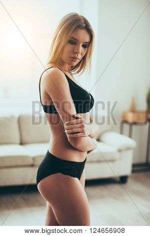 Sensual and tender. Beautiful young woman in black lingerie keeping eyes closed while standing against window at home