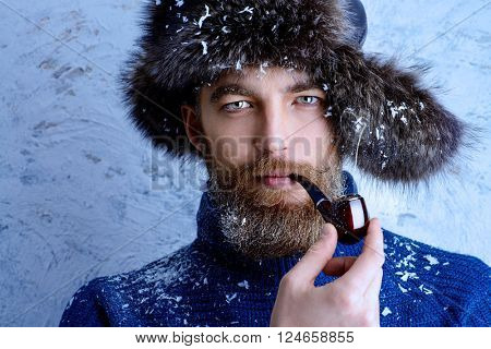 Portrait of a handsome brutal man with beard and mustache dressed in winter clothes, covered with snow.