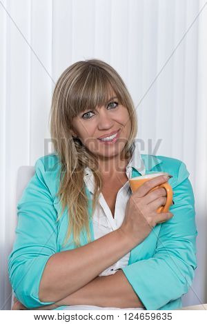A smiling businesswoman is holding a cup of coffee while sitting at a table in the office. The woman is looking to the camera.