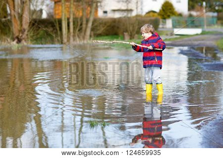 Beautiful little kid boy in rain boots playing with selfmade fishing rod by a puddle on warm spring day. Active leisure for children. Child having fun outdoors.