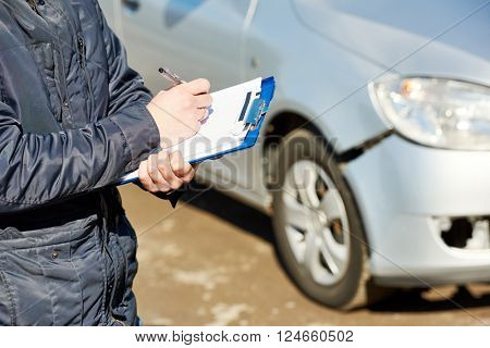 Insurance agent recording car damage on claim form