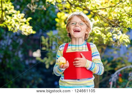 Happy little kid boy with glasses, books, apple and backpack on his first day to school or nursery. Child outdoors on warm sunny day, Back to school concept