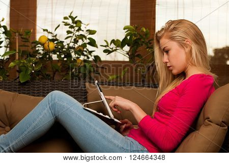 Woman Comfortable Sitting On Sofa And Using Tablet Computer.