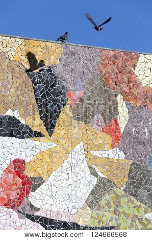 The pigeon flying over colorful wall of mosaic in the city of Seattle (Washington).
