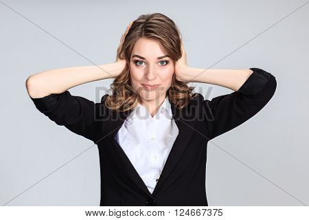 The young woman's portrait with happy emotions on gray background. girl covers his ears hands