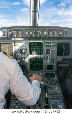 Pilot in the cockpit pulling the aircraft throttle