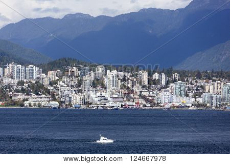 The view of West Vancouver with a boat passing by (British Columbia Canada).