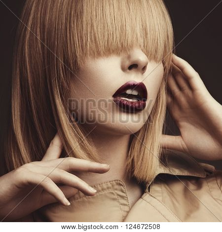 Beautiful blonde woman in a bright coat and dark lips showing different poses. Beauty face. Picture taken in the studio.